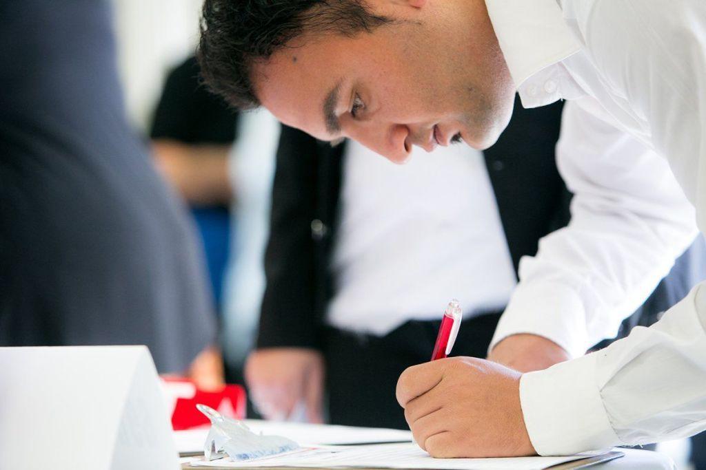 Hombre-de-negocios-agachado-firmando-un-documento-sobre-una-mesa