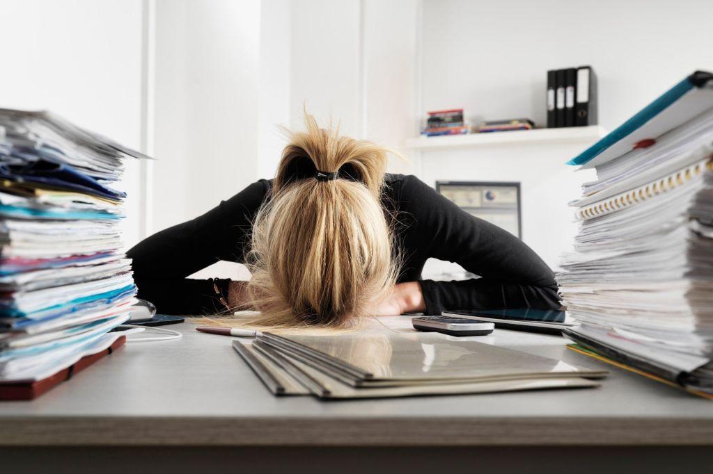 Mujer-agobiada-con-la-cabeza-encima-de-una-mesa-con-varias-carpetas-con-informes
