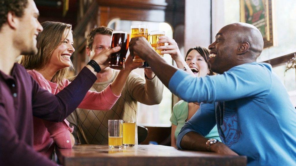 Varios-amigos-en-un-bar-brindando-con-cervezas-y-otras-bebidas