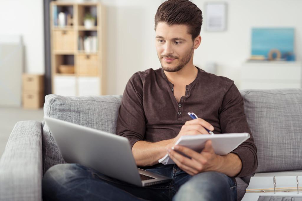 mann mit laptop und unterlagen in seiner wohnung