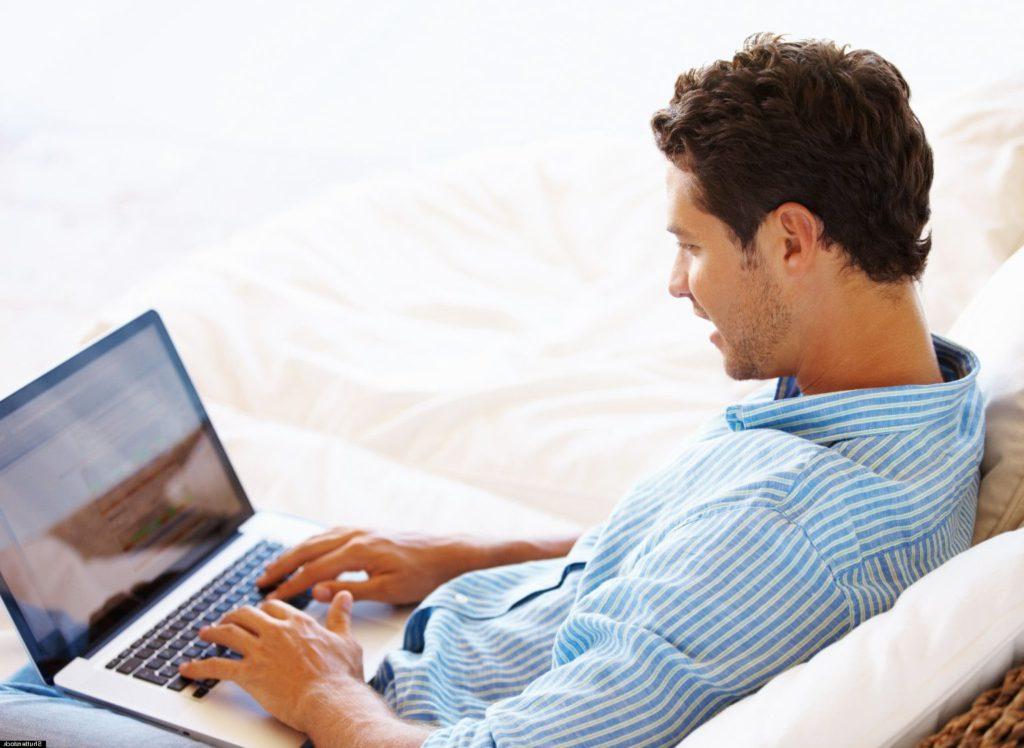 Hombre-sentado-mirando-a-su-laptop-y-escribiendo-en-el