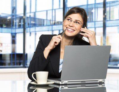 mujer-feliz-y-sonriente-en-oficina-con-escritorio-y-computadora