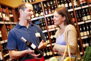 Sommelier im Weinhandel berät eine Frau beim Weinkauf