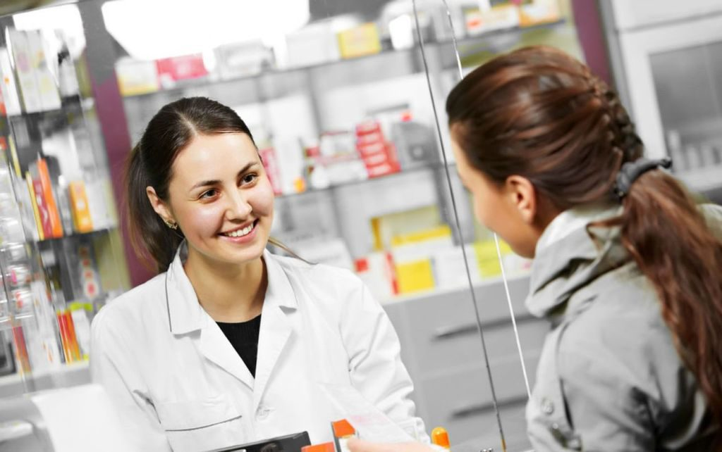 Una-dependienta-de-un-negocio-hablando-con-una-cliente-a-traves-de-un-cristal-en-un-comercio