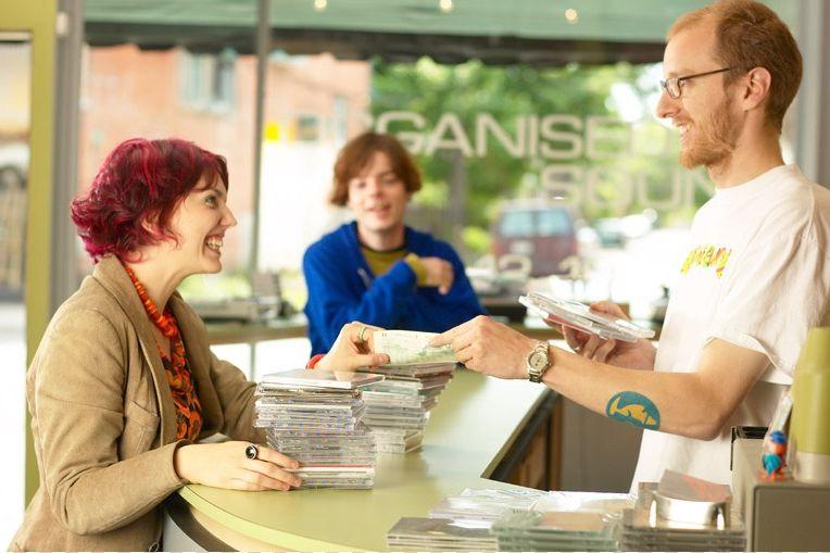 Un-vendedor-cobrando-a-una-cliente-una-compra-de-muchos-CDs