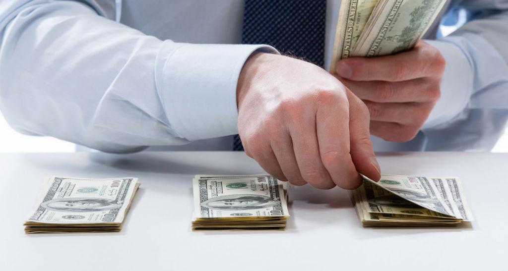 Hombre-con-camisa-poniendo-un-billete-sobre-una-mesa-en-la-que-hay-tres-montones-de-dinero