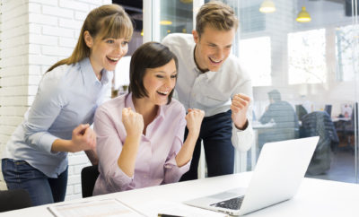 Happy Successful  business team in office, with arms up